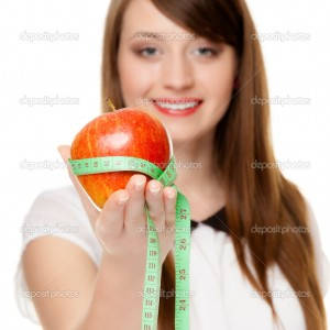 Diet and nutrition. Happy young woman holding apple fruit with measure tape isolated on white. Girl recommending healthy food.
